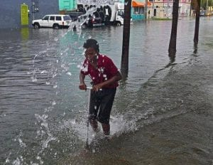 A young boy has fun with his razor scooter during the flood rains