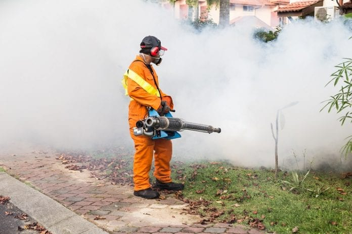 Worker spraying mosquito control - Caribbean National Weekly News